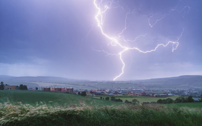 How to photograph lightnings: a lightning with a city in the foreground.